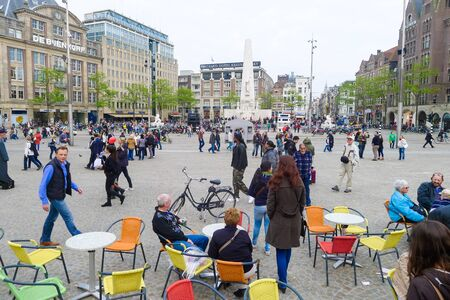 dam square: Amsterdam, The Netherlands May 30 2013: Many tourists and locals gather in Dam Square in Amsterdam city
