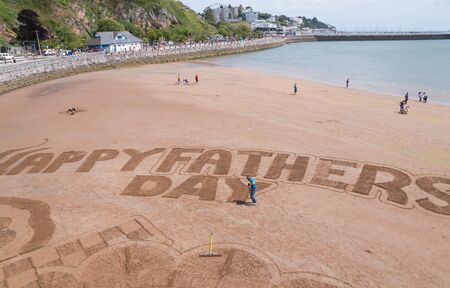 sand writing: Scarborough, United Kingdom June 21, 2015: Man writing fathers day message in the sand on Scarborough Beach while families enjoy the day Editorial