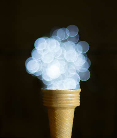 forced perspective: Ice cream cone with defocused lights Stock Photo