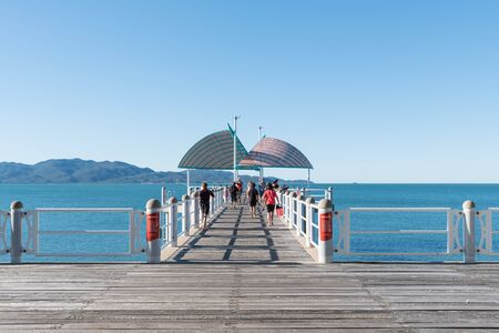 warm water fish: Townsville, Australia - August 4, 2016: Families and children fishing from pier at the beach on a warm winters day in North Queensland with Magnetic Island in the background.