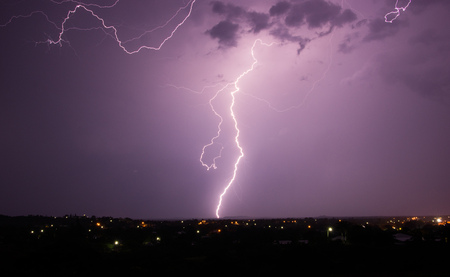 A tropical thunder storm over a country town with lightning strike Stock Photo