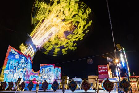 carnival ride: Charters Towers, Australia: August 2, 2016 - A colourful carnival ride spinning very fast high in the air.
