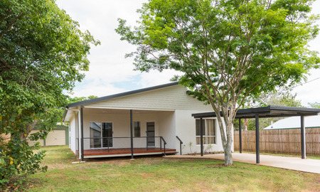 New contemporary style home with carport, trees and garden