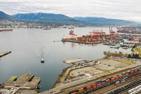 hundreds: Vancouver, Canada - January 28, 2017: Vancouver Port with hundreds of shipping containers and mountains in the background Editorial