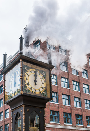 The historic steam clock strikes midday in Gastown, downtown Vancouver, with jets of steam rising from the clock