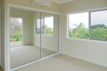 新しい寝室エアコンと床のカーペットに新たに塗られた壁