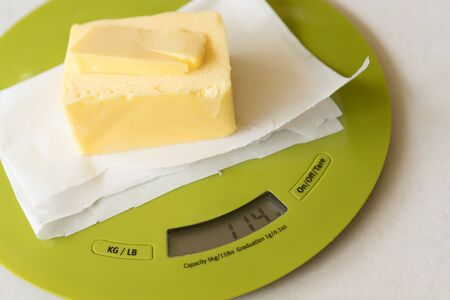 Stick of butter on digital scale in preparation for baking
