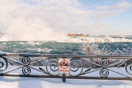 Danger sign on frozen railing at Niagara Falls, Canada
