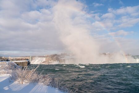 Tourists at Niagara Falls, Canada with snow and ice and rainbow. Stock Photo