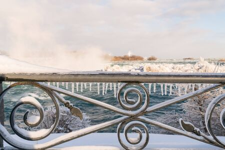 Icicles on handrail at Niagara Falls, Canada, falls in background