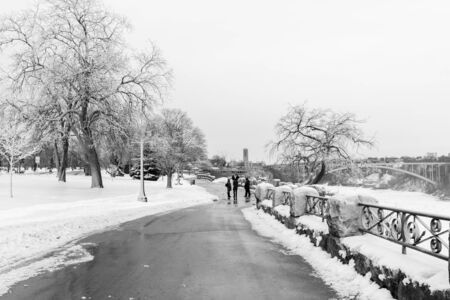 Tourists viewing Niagara Falls in winter with frozen trees, snow and ice. 写真素材