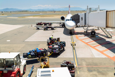 Crew preparing to load luggage onto plane in preparation for takeoff at Townsville airport, North Queensland, Australia