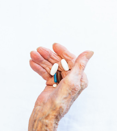 Aged lady holding many pills and capsules