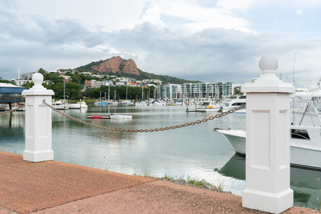 Boats in Townsville Marina with Castle Hill in background, focus on bollards Stock Photo
