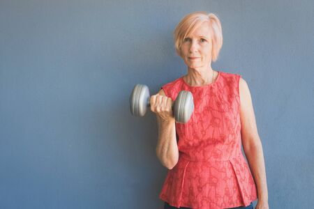 Mature woman keeping fit by lifting weights at home