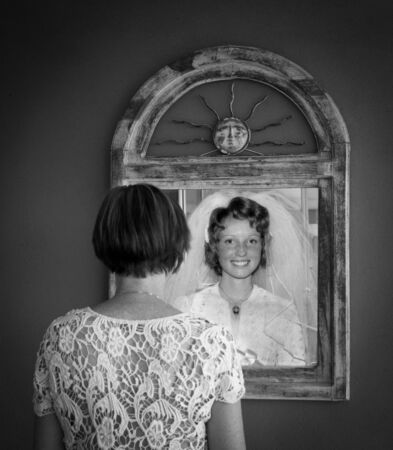 Older woman looking at younger reflection as a bride