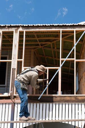 Carpenter working on old timber framed high set Queenslander style house Archivio Fotografico