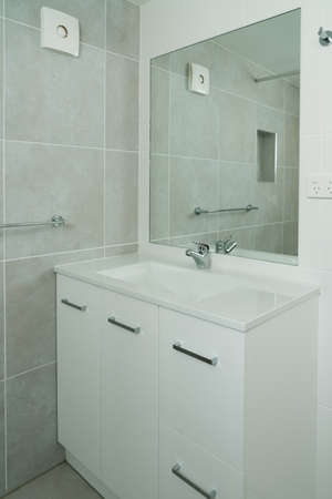 Newly renovated ensuite bathroom with basin, mirror and tiled walls Archivio Fotografico
