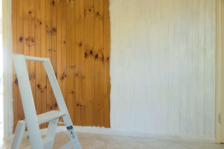 Natural timber tongue and groove wall being painted off-white