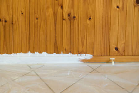 Preparation to paint timber wall with drop sheet to protect tiled floor