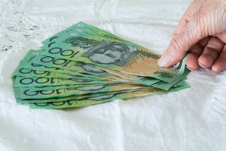 Person placing and counting money, one hundred dollar notes, Australian currency