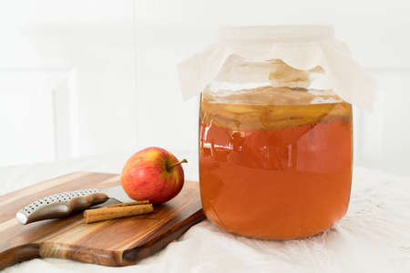 Ingredients to make apple and cinnamon kombucha drink, sweet black tea with scoby fermenting contains probiotics