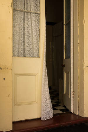Curtain blowing in open antique doorway to a bedroom in an old Queenslander style house Archivio Fotografico