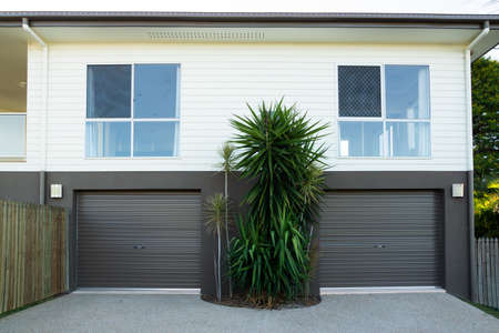 New contemporary double storey house with double garage roller doors Archivio Fotografico