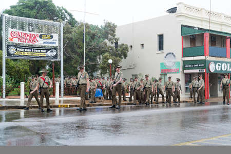 Charters Towers, Australia - April 25, 2019: Soldiers of the 1st Battalion, Royal Australian Regiment preparing to march in the rain on Anzac Day