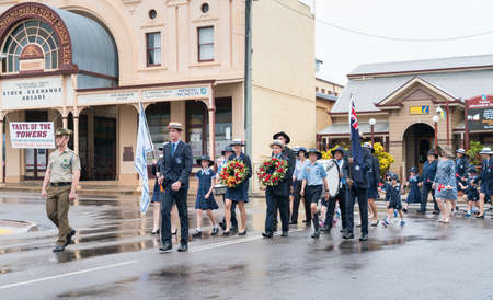 Charters Towers, Australia - April 25, 2019: School children marching in the rain on Anzac Day carrying wreaths and poppies