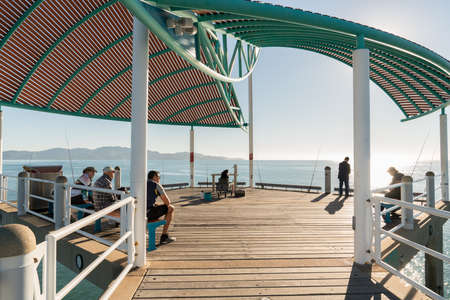 Townsville, Australia - June 20, 2019: Fishermen in the morning on a warm winter's day on the Strand jetty, Townsville