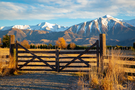 A wooden gate that leads to the farm, under the beautiful snow-capped mountains, is closed