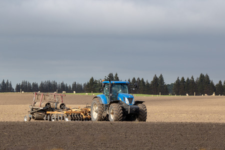 A blue tractor with attached plough on a field in New Zealand