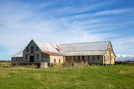 An old wooden and corrugated iron woolshed or shearing shed still sits on a rural farm in New Zealand 免版税图像