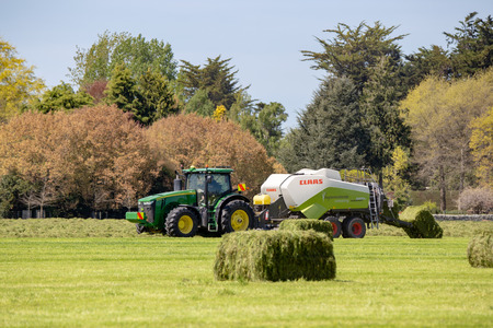 Geraldine, Canterbury, New Zealand - October 21 2018: A farming scene with a John Deere tractor and a Claas baler making hay bales in spring