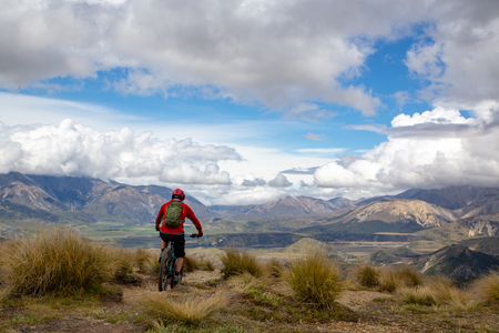 A mountain biker rides along the ridge and descends with beautiful landscape below