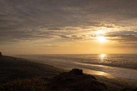 The sun rises over the ocean and disappears into the cloudy sky at Dorie, Canterbury, New Zealand