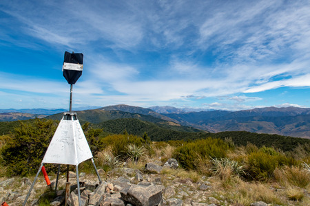 The trig station at the summit of Mt Richardson with a view of the surrounding mountains, New Zealand