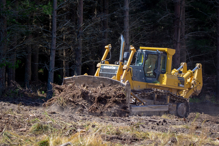 Windwhistle, Canterbury, New Zealand - February 9 2019: A large yellow bulldozer pushes stumps and tree roots into piles to prepare a forestry site for replanting