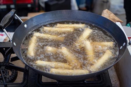 Spring rolls deep frying in hot boiling oil in a wok