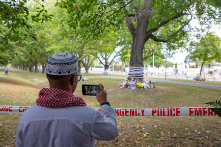 Christchurch, Canterbury, New Zealand, March 22 2019: A Muslim man takes photos of the floral tributes left in front of the Masij Al Noor in sympathy of those killed one week ago