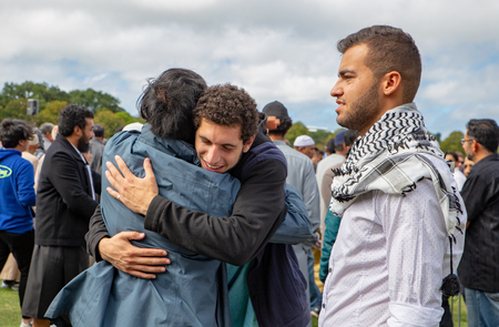 Christchurch, Canterbury, New Zealand, March 22 2019: Muslim men greet each other at the prayer service in Hagley Park one week after the mosque shootings