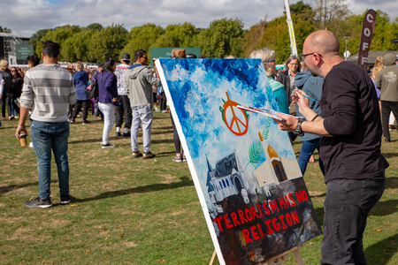 Christchurch, Canterbury, New Zealand, March 29 2019: An artist paints for peace at the memorial service for the victims of the Christchurch mosque shootings
