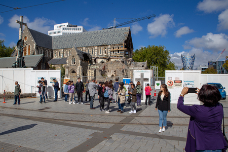 Christchurch, New Zealand, March 29 2019: Asian tourists take photos of the earthquake damaged Christchurch Cathedral in the Christchurch Square 新闻类图片