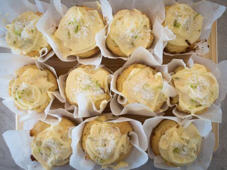 Freshly baked coconut and lime muffins cool and set on a kitchen benchtop ready for afternoon tea