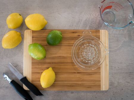 Using a glass hand juicer and zester to extract juice and rind from lemons and limes for a recipe 免版税图像