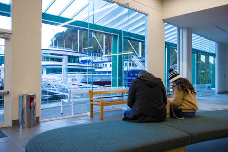 Milford Sound, Fiordland, New Zealand, June 20 2020: Two New Zealand tourists in the ferry terminal at Milford Sound, waiting to go on their scenic cruise in the fjord