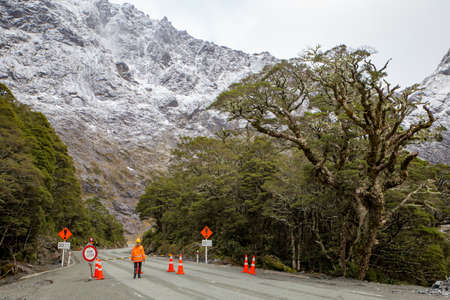 Milford Sound, New Zealand, June 20 2020: The road through the Homer Tunnel becomes one way for tourists traveling in and out. A female road worker.