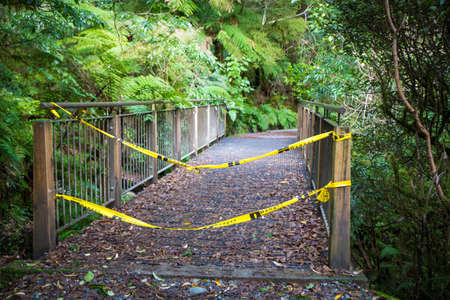 A Department of Conservation hiking track in Milford Sound has 'No Entry' tape across the bridge to signal hazards ahead with a washed out bridge