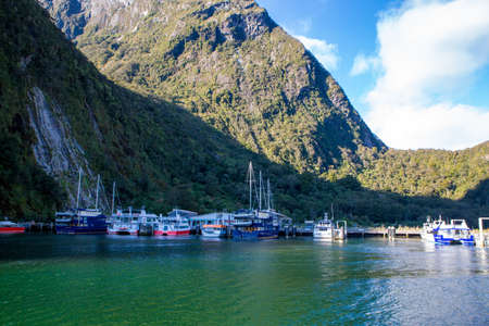 Milford Sound, Fiordland, New Zealand, June 20 2020: Cruise boats docked at the wharf in Milford Sound. Tourism is at a low as a result of Corona Virus and no overseas tourists.